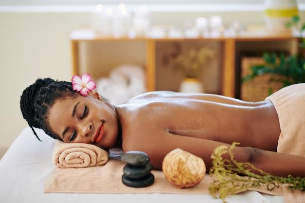 Mooie jonge zwarte vrouw met bloem in haar haar rustend op bed in de spa salon na een ontspannende rugmassage met oliën