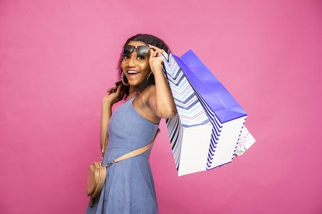 Mooie jonge zwarte vrouw met boodschappentassen die zich opgewonden voelt