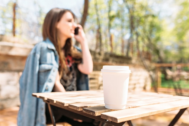 Mooie jongedame gekleed in spijkerjasje praat aan de telefoon in park in zonlicht met charmante glimlach. op de voorgrond een kopje koffie. zonnige dag, goed humeur.