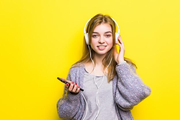 Mooie jongedame genieten met luisteren naar de muziek in de koptelefoon