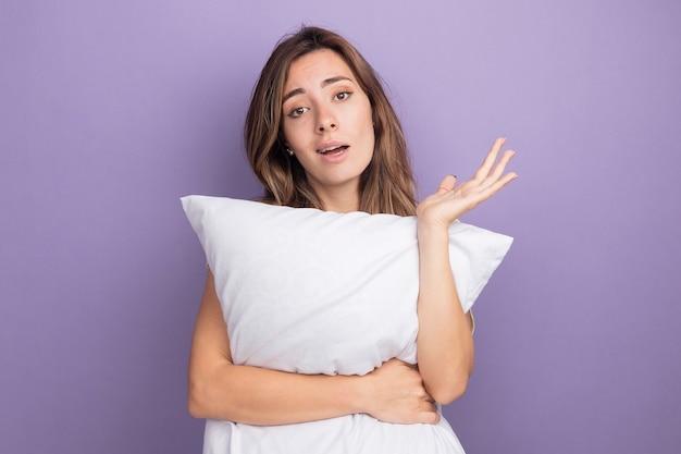 Mooie jongedame in beige t-shirt met wit kussen kijkend naar camera met zelfverzekerde uitdrukking met opgeheven arm over paarse achtergrond