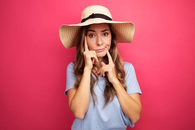 Mooie jongedame in blauw t-shirt en zomerhoed camera kijken met sceptische uitdrukking