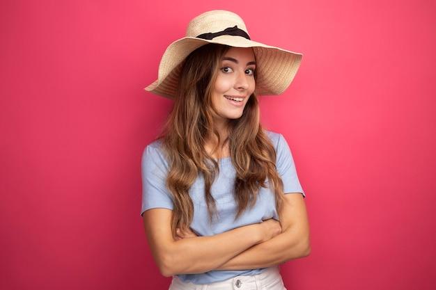 Mooie jongedame in blauw t-shirt en zomerhoed die naar de camera kijkt, blij en positief glimlacht met gekruiste armen