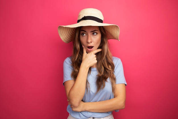 Mooie jongedame in blauw t-shirt en zomerhoed die opzij kijkt verbaasd over roze achtergrond