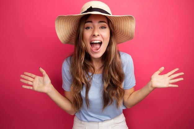 Mooie jongedame in blauw t-shirt en zomerhoed kijkend naar camera gek blij en opgewonden schreeuwend met opgeheven armen over roze achtergrond