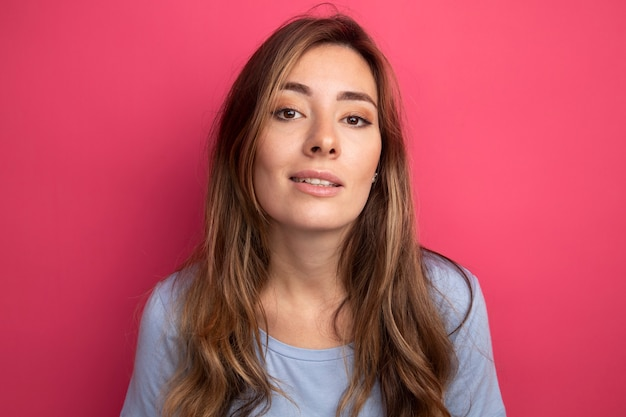 Mooie jongedame in blauw t-shirt kijkend naar camera glimlachend zelfverzekerd over roze achtergrond