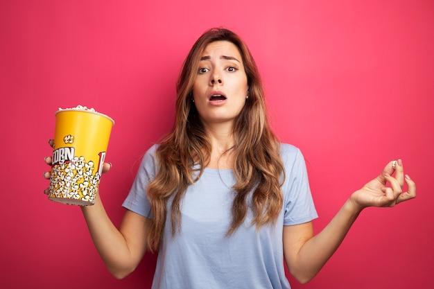Mooie jongedame in blauw t-shirt met emmer met popcorn kijkend naar camera verrast over roze achtergrond