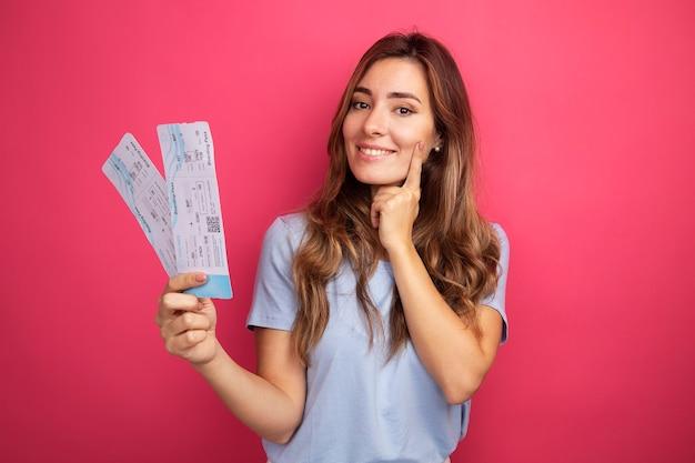 Mooie jongedame in blauw t-shirt met vliegtickets die naar de camera kijkt en vrolijk lacht over roze achtergrond