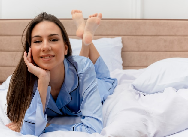 Mooie jongedame in blauwe pyjama's liggend op bed rusten kijken camera glimlachen met blij gezicht genieten van ochtend tijd in slaapkamer interieur op lichte achtergrond