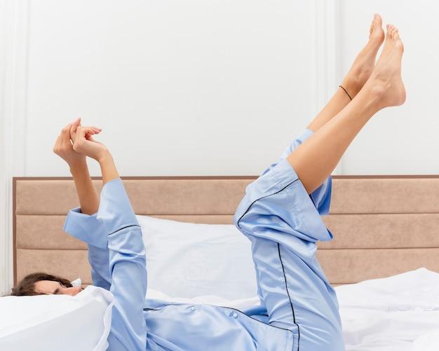 Mooie jongedame in blauwe pyjama tot op bed met verhoogde benen rustend op zachte kussens gelukkig en positief genieten van de ochtend tijd in slaapkamer interieur op lichte achtergrond