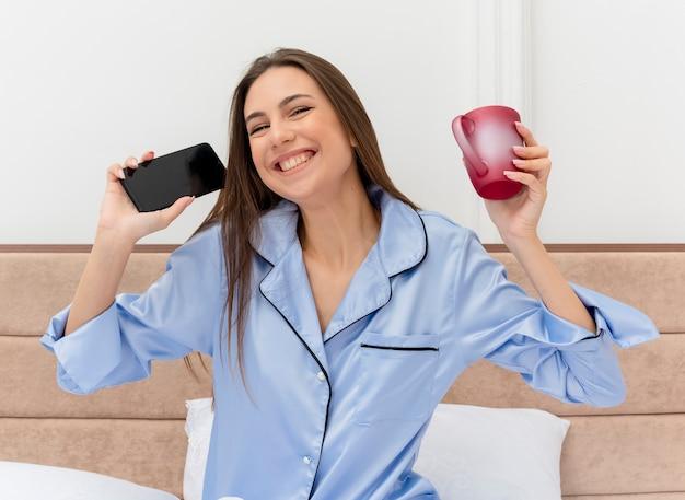 Mooie jongedame in blauwe pyjama zittend op bed met kopje koffie bedrijf smartphone kijken camera blij en opgewonden glimlachend vrolijk in slaapkamer interieur op lichte achtergrond