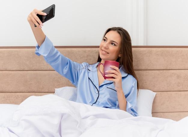 Mooie jongedame in blauwe pyjama zittend op bed met kopje koffie selfie glimlachend met blij gezicht in slaapkamer interieur op lichte achtergrond doen