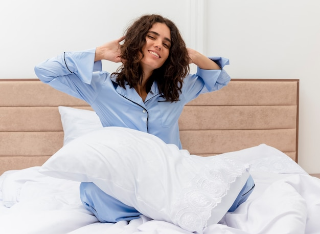 Mooie jongedame in blauwe pyjama zittend op bed met kussen dat zichzelf uitrekt en glimlachend wakker wordt in het interieur van de slaapkamer