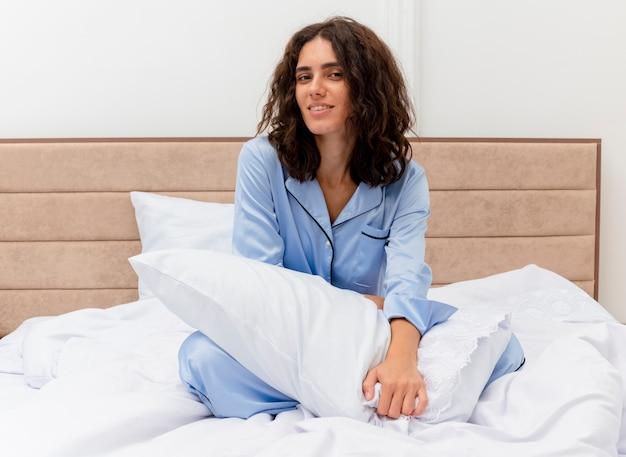 Mooie jongedame in blauwe pyjama zittend op bed met kussen kijken camera blij en positief glimlachend vrolijk in slaapkamer interieur
