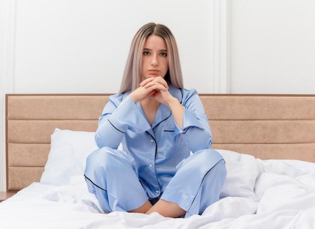 Mooie jongedame in blauwe pyjama zittend op bed met serieus gezicht hand in hand samen in slaapkamer interieur