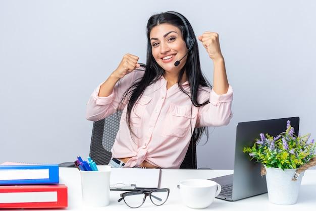 Mooie jongedame in casual kleding met koptelefoon en microfoon blij en opgewonden gebalde vuisten zittend aan de tafel met laptop over witte muur werken op kantoor