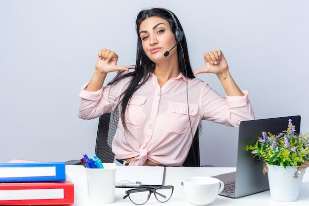 Mooie jongedame in casual kleding met koptelefoon en microfoon die er zelfverzekerd uitziet en met de vingers naar zichzelf wijst terwijl ze aan de tafel zit met laptop over witte muur die op kantoor werkt