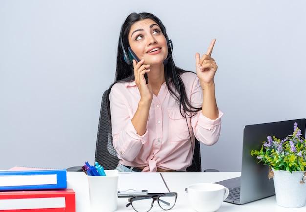Mooie jongedame in casual kleding met koptelefoon en microfoon zittend aan de tafel met laptop opzoeken glimlachend wijzend met de vinger omhoog over witte achtergrond werken in kantoor