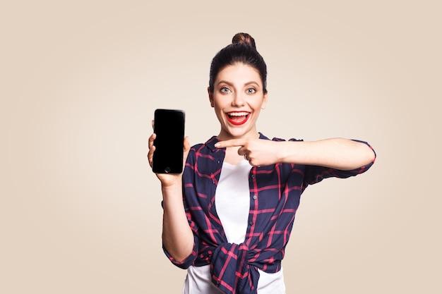 Mooie jongedame in casual stijl met telefoon die naar de camera kijkt en een telefoondisplay met vinger laat zien. studio-opname op beige achtergrond.