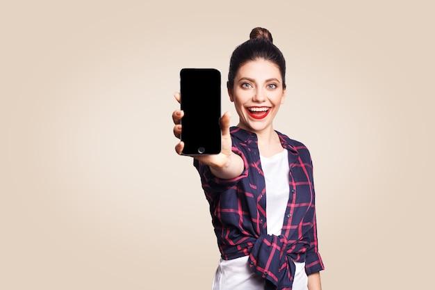 Mooie jongedame in casual stijl met telefoon die naar de camera kijkt en telefoonweergave toont. studio-opname op beige achtergrond.