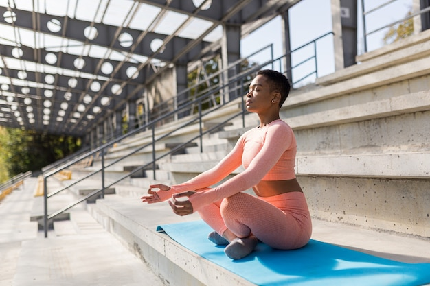Mooie jongedame in een roze trainingspak mediterend in het stadion in de ochtend, fitnesstrainer rust na de training