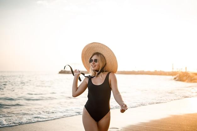 Mooie jongedame in een zwarte zwembroek en hoed met bril loopt langs het strand bij zonsondergang. het concept van zeerecreatie. selectieve focus