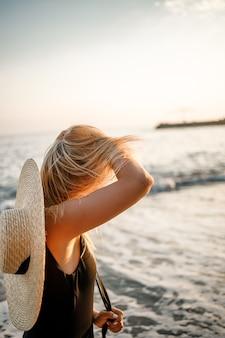 Mooie jongedame in een zwarte zwembroek en hoed met bril loopt langs het strand in turkije bij zonsondergang. het concept van zeerecreatie. selectieve focus