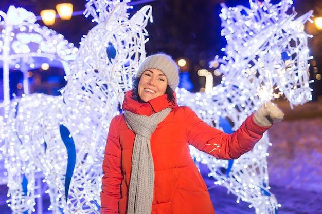 Mooie jongedame in gebreide muts en sjaal staan in de stad met bengalen licht, sparkler. conceptviering en kerstmis.
