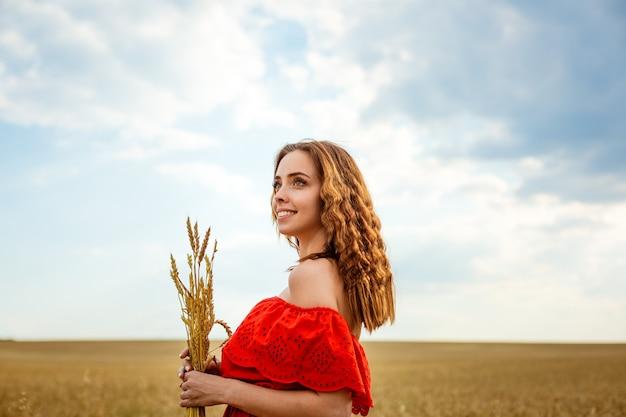 Mooie jongedame in gouden tarweveld gelukkige vrouw in rode jurk genieten van het leven in veld natuur b...