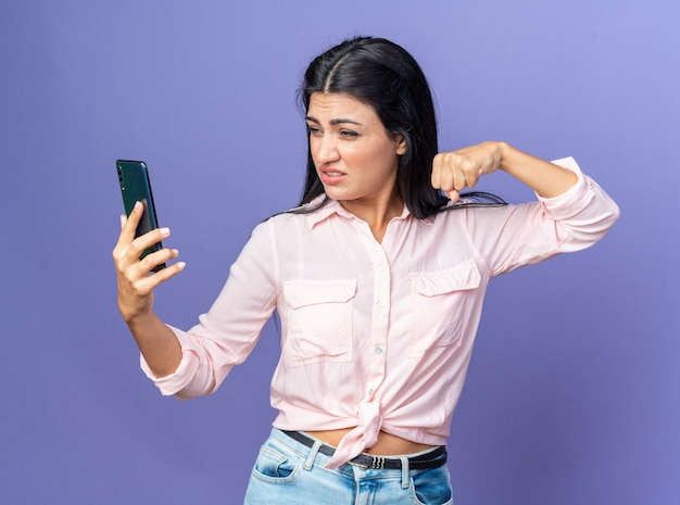Mooie jongedame in vrijetijdskleding die selfie maakt met smartphone die gebalde vuist toont