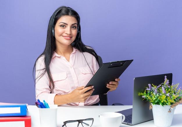 Mooie jongedame in vrijetijdskleding met een hoofdtelefoon met microfoon die klembord vasthoudt en glimlachend zelfverzekerd aan de tafel zit met een laptop op blauw