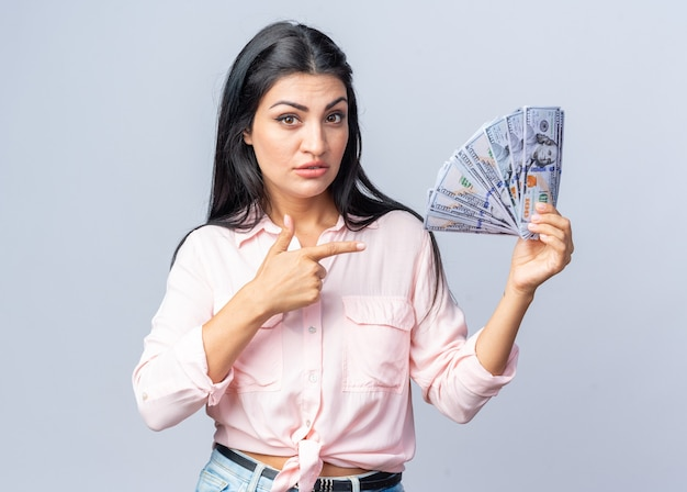 Mooie jongedame in vrijetijdskleding met een hoop dollargeld wijzend met de wijsvinger naar geld met een serieus gezicht over een witte muur
