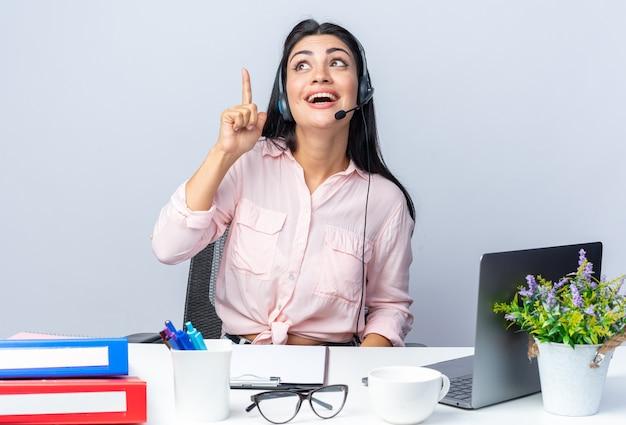 Mooie jongedame in vrijetijdskleding met koptelefoon en microfoon die blij en vrolijk aan de tafel zit met een laptop op wit