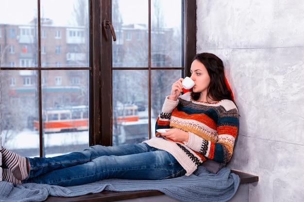 Mooie jongedame in warme gebreide trui liggend op de kussens op de vensterbank en een kopje koffie drinken