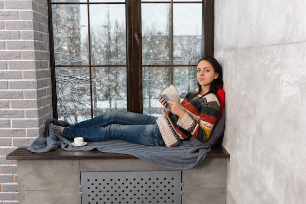 Mooie jongedame in warme gebreide trui liggend op de vensterbank met kussens en deken en kijkend naar de camera tijdens het lezen van een boek