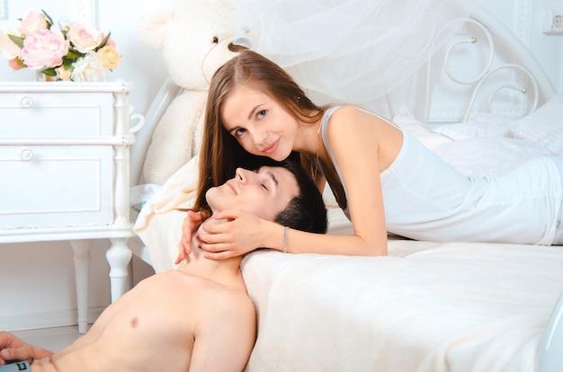 Mooie jongedame knuffelen gezicht van haar vriendje en kijken naar de camera op een bed liggen