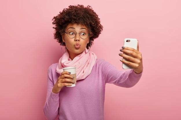 Mooie jongedame met afro kapsel, houdt de lippen gevouwen, blaast kus op camera van smartphone, neemt selfie portret
