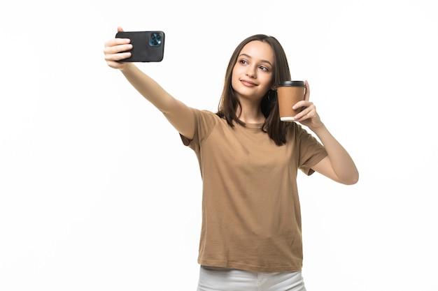 Mooie jongedame met behulp van smartphone selfie tijd, koffiekopje en mobiele telefoon geïsoleerd op wit te houden