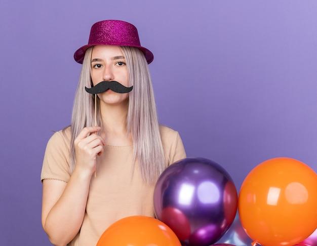 Mooie jongedame met feestmuts met ballonnen met nepsnor op stok geïsoleerd op blauwe muur