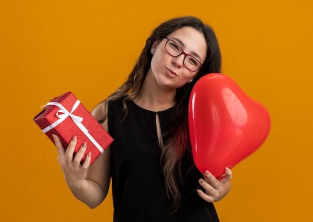 Mooie jongedame met rode ballon in hartvorm en cadeau blij en vrolijk lachend om valentijnsdag te vieren