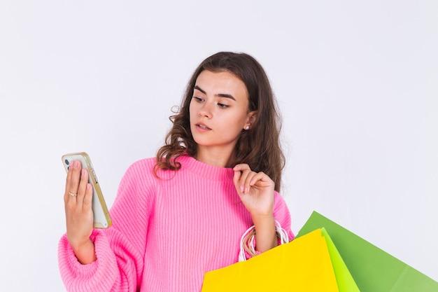 Mooie jongedame met sproeten lichte make-up in trui op witte muur met boodschappentassen en mobiele telefoon