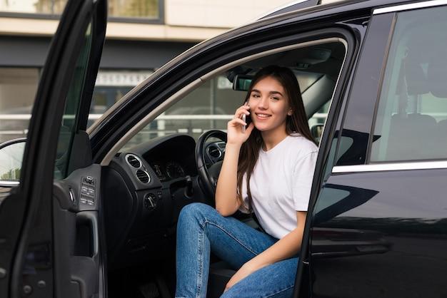 Mooie jongedame praten over de telefoon zit in de auto