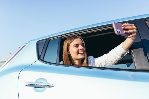 Mooie jongedame praten over video-oproep zittend in de auto steekt zijn hand met de telefoon uit het raam