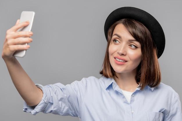Mooie jongedame smartphone kijken terwijl het maken van selfie geïsoleerd