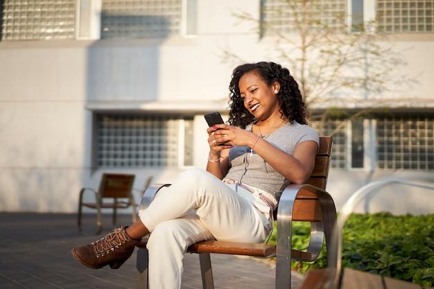Mooie jongedame typen op mobiele telefoon zittend op de bank glimlachend gemengd ras vrouw met smartphone...