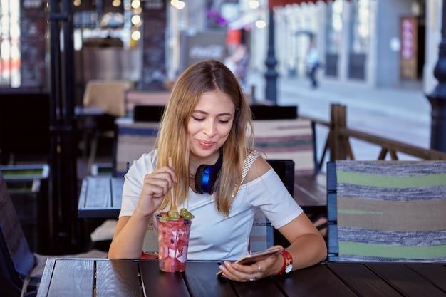 Mooie jongedame van ongeveer 25 jaar met blond en lang haar zit in een straatcafé en glimlacht terwijl ze een dessert eet met een mobiele telefoon in de hand.