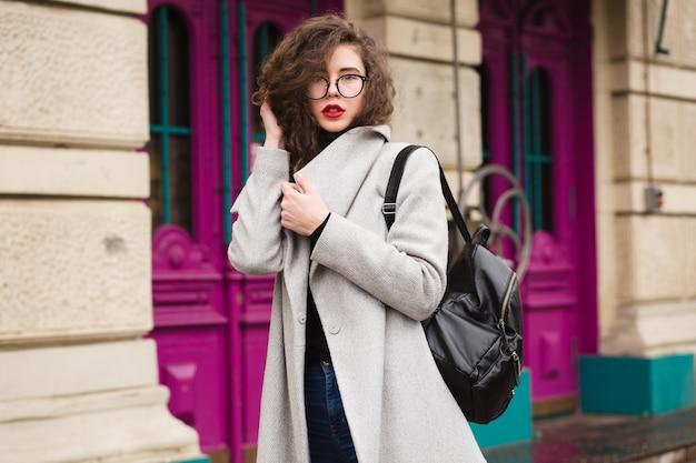 Mooie jongedame wandelen in de stad straat in grijze jas, herfst fashion stijl, bril, rugzak,