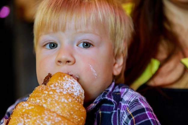 Mooie jongen croissant broodje chocolade eten de tafel in een papieren zak close-up hand kleine jongen