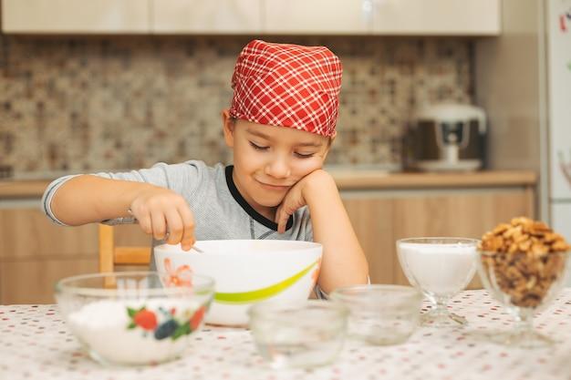 Mooie jongen die een cake met noten kookt.