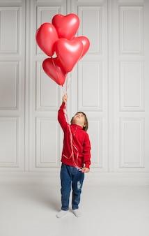 Mooie jongen die in jeans en sweater hartballons houdt en op witte achtergrond omhoog kijkt